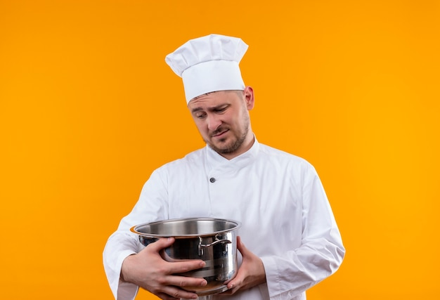 Thoughtful young handsome cook in chef uniform holding boiler and looking at it on isolated orange space
