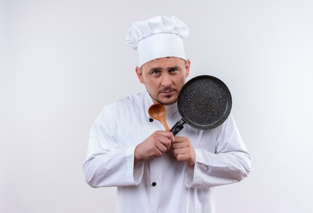 Giovane cuoco bello premuroso in cucchiaio e padella della holding dell'uniforme del cuoco unico isolati su spazio bianco