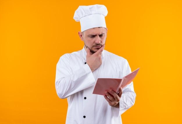オレンジ色のスペースで隔離のあごに手でメモ帳を保持し、見ているシェフの制服を着た思いやりのある若いハンサムな料理人