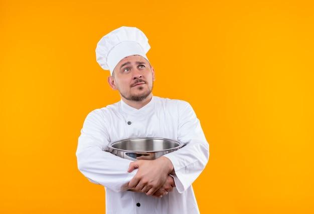 孤立したオレンジ色の空間を見上げるボイラーを保持しているシェフの制服を着た思いやりのある若いハンサムな料理人