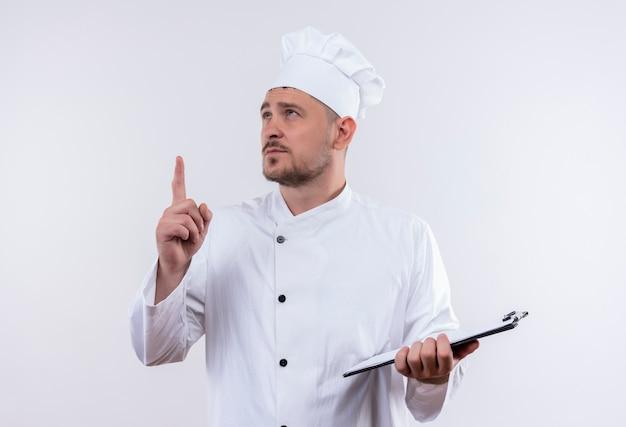 孤立した白いスペースを見て、上向きクリップボードを保持しているシェフの制服を着た思いやりのある若いハンサムな料理人