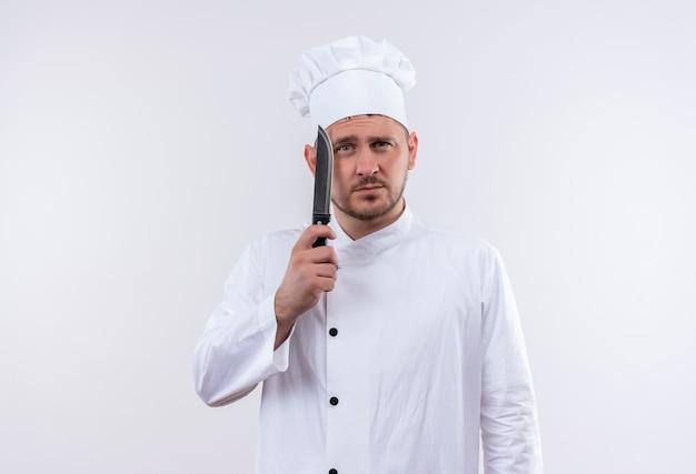 白いスペースで隔離のナイフを保持しているシェフの制服を着た思いやりのある若いハンサムな料理人