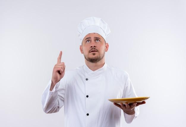 孤立した白いスペースを見て、上向きにプレートを保持しているシェフの制服を着た思いやりのある若いハンサムな料理人
