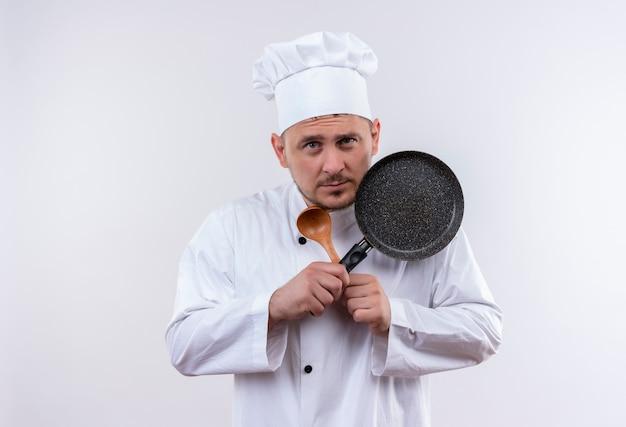 白いスペースで隔離のスプーンとフライパンを保持しているシェフの制服を着た思いやりのある若いハンサムな料理人