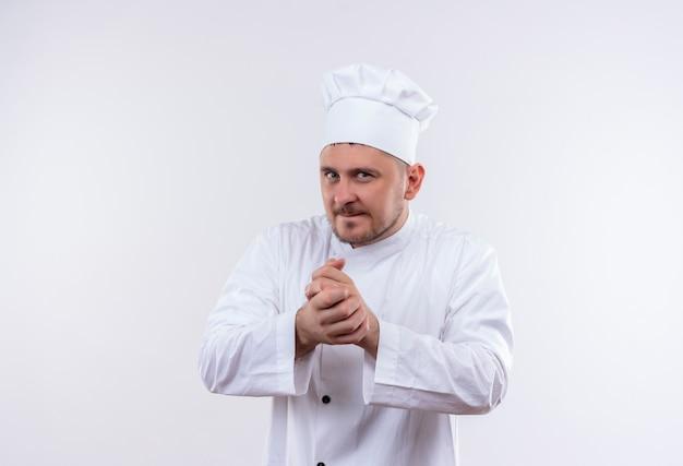 孤立した白いスペースで手を一緒に保つシェフの制服を着た思いやりのある若いハンサムな料理人