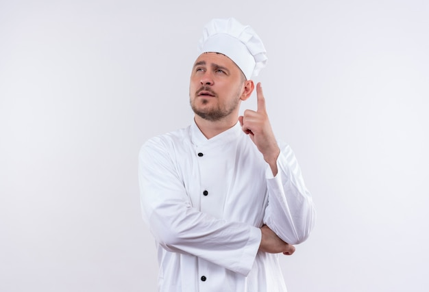 孤立した白いスペースで上げられた指で見上げるシェフの制服を着た思いやりのある若いハンサムな料理人