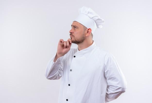 シェフの制服を着た思いやりのある若いハンサムな料理人は、白いスペースで隔離された側を見て縦断ビューで立っているあごに手を置きます