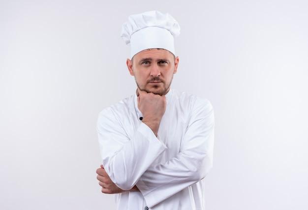 白いスペースで隔離のあごの下に手を置くシェフの制服を着た思いやりのある若いハンサムな料理人