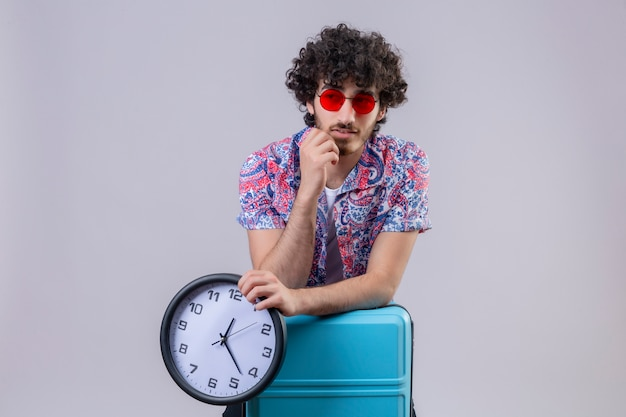 Riflessivo giovane viaggiatore riccio bello uomo che indossa occhiali da sole e tenendo l'orologio e mettendo le braccia sulla valigia con la mano sul mento sul muro bianco isolato con spazio di copia
