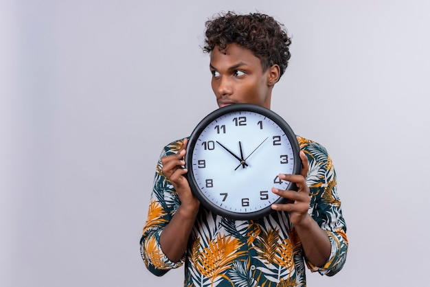 Thoughtful young handsome dark-skinned man with curly hair in leaves printed shirt holding wall clock showing time on a white background