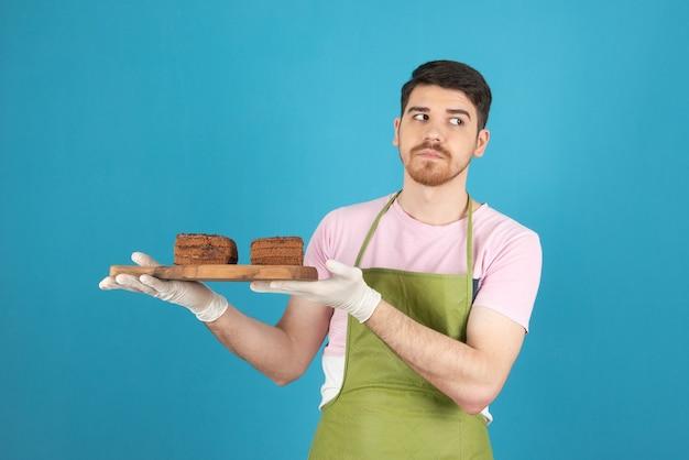 ケーキのスライスを保持し、目をそらしている思いやりのある若いハンサムな男。