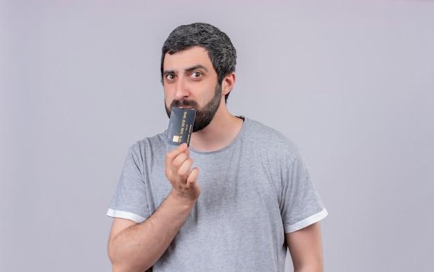 Giovane uomo bello premuroso che mette la carta di credito sulla bocca isolata sulla parete bianca