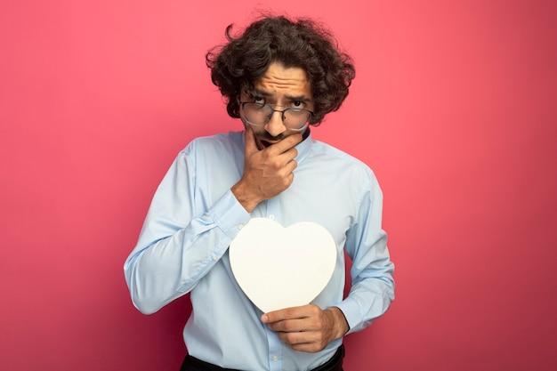 Задумчивый молодой красавец в очках держит форму сердца, глядя вперед, держа руку на рте, изолированном на розовой стене