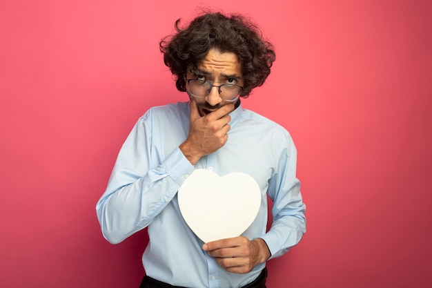 Riflessivo giovane uomo bello con gli occhiali che tengono a forma di cuore guardando davanti tenendo la mano sulla bocca isolata sul muro rosa