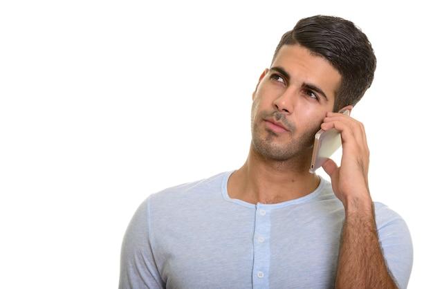 Задумчивый молодой красивый персидский мужчина разговаривает по мобильному телефону