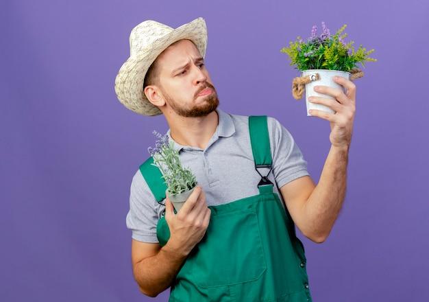 コピースペースと紫色の壁に分離された植木鉢を保持し、見て帽子と制服を着た思いやりのある若いハンサムなスラブの庭師