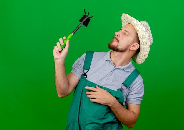 Задумчивый молодой красивый славянский садовник в форме и шляпе держит и смотрит на грабли