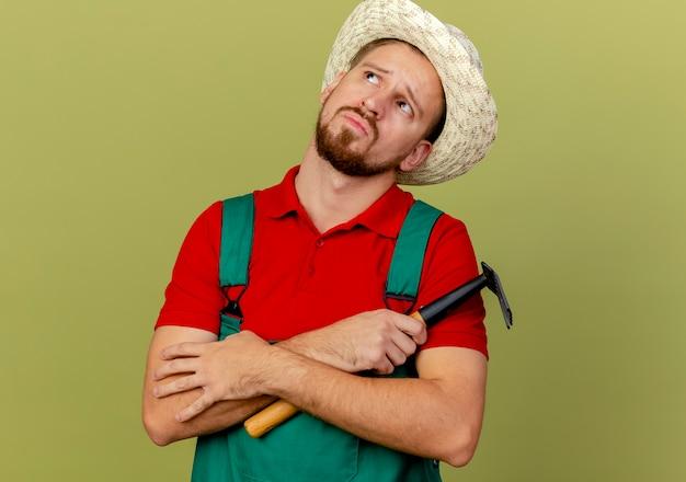 思いやりのある若いハンサムなスラブの庭師の制服と帽子を握って手を交差させて熊手を持って見上げるオリーブグリーンの壁にコピースペースで隔離