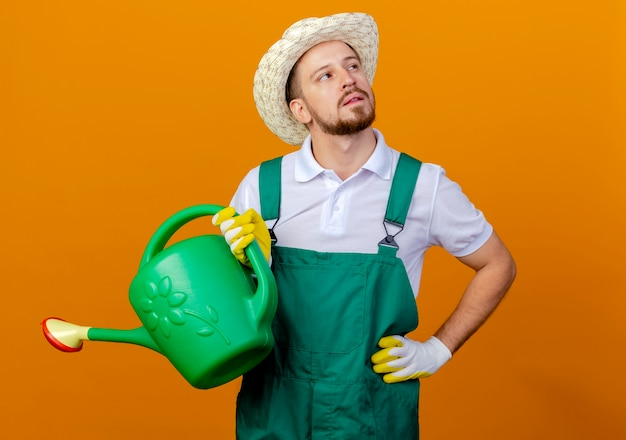 Thoughtful young handsome slavic gardener in uniform and hat holding watering can keeping hand on waist looking at side isolated on orange wall