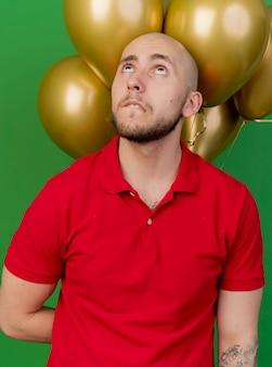 Задумчивый молодой красивый славянский тусовщик, держащий воздушные шары за спиной, глядя вверх прикусив губу, изолирован на зеленом фоне