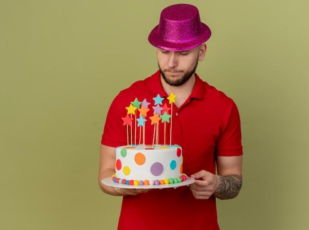 사려 깊은 젊은 잘 생긴 슬라브 파티 남자 들고 파티 모자를 쓰고 복사 공간이 올리브 녹색 배경에 고립 된 생일 케이크를보고