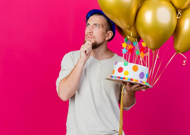 Thoughtful young handsome slavic party guy wearing party hat holding balloons and birthday cake with stars touching chin looking at side isolated on pink wall with copy space