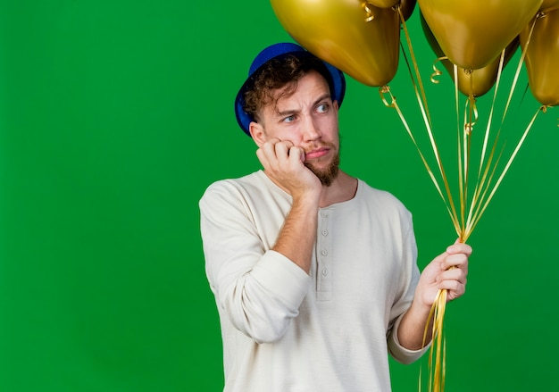 Ragazzo di partito slavo bello giovane premuroso che indossa il cappello del partito che tiene palloncini mettendo la mano sul mento guardando il lato isolato su sfondo verde con spazio di copia