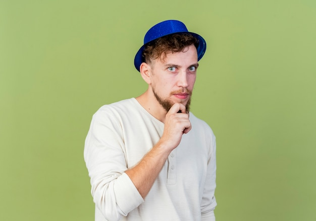 Ragazzo di partito slavo bello giovane premuroso che indossa il cappello del partito che guarda l'obbiettivo che mette la mano sul mento isolato su fondo verde oliva con lo spazio della copia