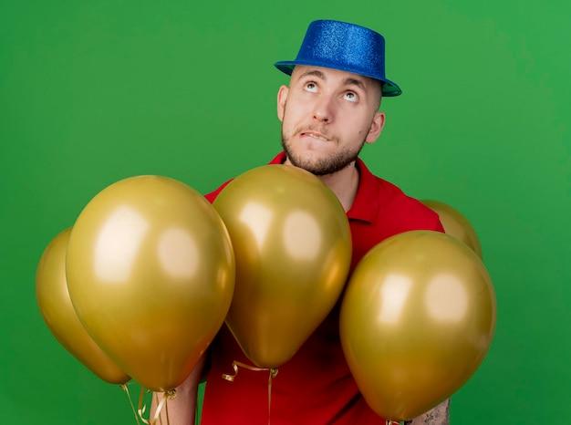 녹색 벽에 고립 된 입술을 물고 풍선 사이에 서있는 파티 모자를 쓰고 사려 깊은 젊은 잘 생긴 슬라브 파티 남자