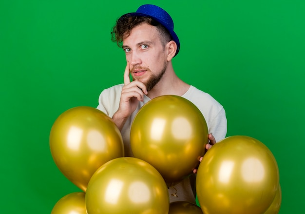 Ragazzo di partito slavo bello giovane premuroso che indossa il cappello del partito in piedi dietro i palloncini che guarda l'obbiettivo che tocca il mento isolato su priorità bassa verde