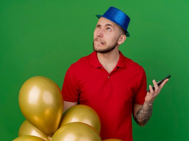 사려 깊은 젊은 잘 생긴 슬라브 파티 사람이 한 눈으로 올려 입술을 물고 휴대 전화를 들고 풍선 뒤에 서있는 파티 모자를 쓰고 녹색 배경에 고립 폐쇄