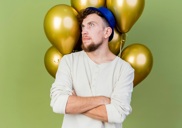 Thoughtful young handsome slavic party guy wearing party hat standing with closed posture in front of balloons looking at side isolated on olive green wall with copy space