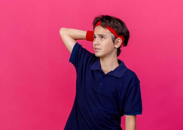 Thoughtful young handsome sporty boy wearing headband and wristbands with dental braces looking up keeping hand behind head isolated on pink wall with copy space