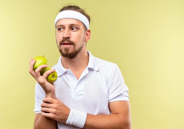 Вдумчивый молодой красивый спортивный мужчина в головной повязке и браслетах держит яблоки и держит запястье, глядя в сторону, изолированную на зеленом пространстве