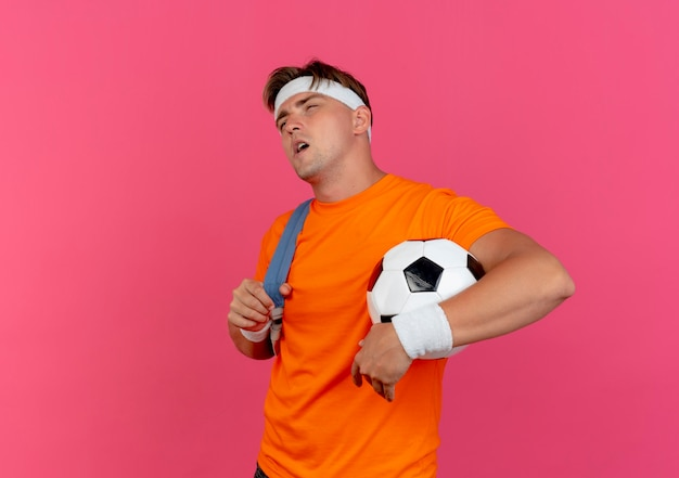 Thoughtful young handsome sporty man wearing headband and wristbands and back bag holding soccer ball and strap of back bag looking straight isolated on pink wall