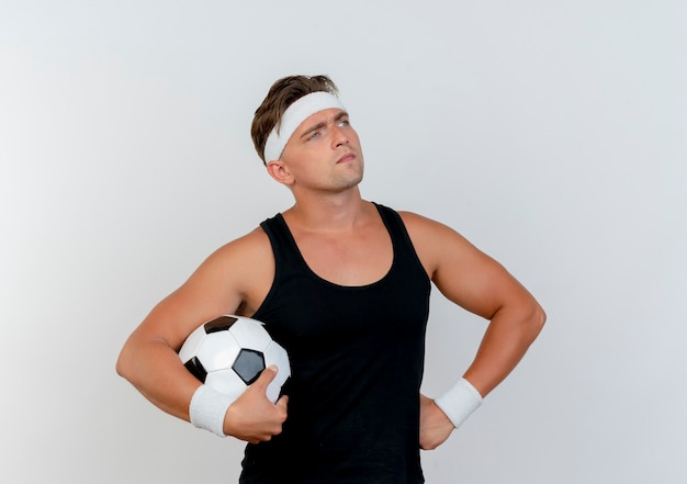Thoughtful young handsome sporty man wearing headband and wristbands holding soccer ball and putting hand on waist looking at side isolated on white wall
