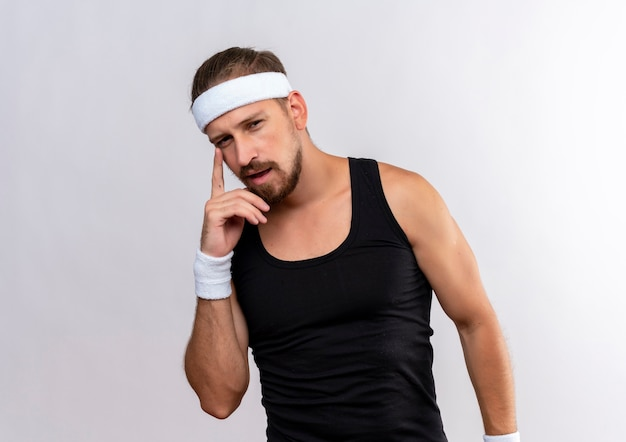 Riflessivo giovane bell'uomo sportivo che indossa la fascia e braccialetti mettendo il dito sul viso cercando isolato su uno spazio bianco