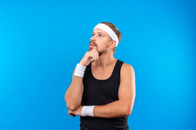Riflessivo giovane bell'uomo sportivo che indossa la fascia e braccialetti mettendo le mani sul mento e sotto il gomito guardando lato isolato su spazio blu