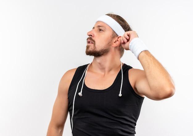 Riflessivo giovane bell'uomo sportivo che indossa la fascia e braccialetti con le cuffie intorno al collo tenendo la mano vicino alla testa guardando il lato isolato su uno spazio bianco