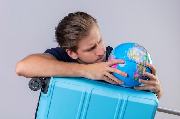 Вдумчивый молодой красивый путешественник, стоящий с чемоданом, держит глобус и смотрит на него с серьезным лицом на белом фоне