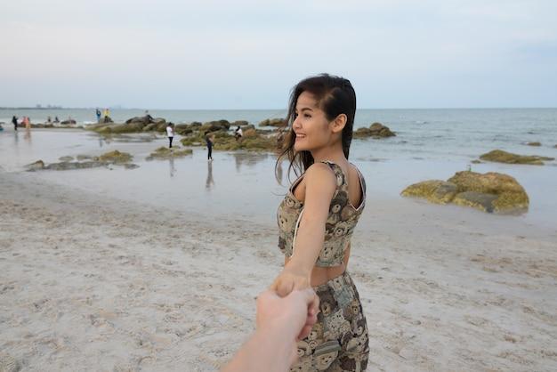 Задумчивая молодая счастливая азиатская женщина улыбается