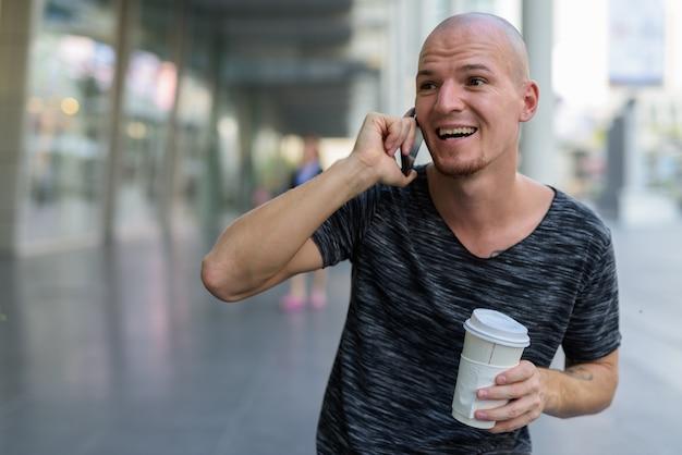 Задумчивый молодой счастливый лысый мужчина улыбается и смеется во время разговора по телефону