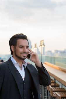 屋上レストランで携帯電話で話しながら笑って思いやりのある若い幸せなインドのビジネスマン