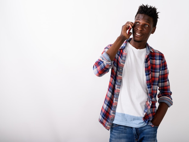 Вдумчивый молодой счастливый человек улыбается и разговаривает по телефону