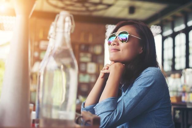 Riflessivo giovane donna pantaloni a vita bassa con gli occhiali seduto al tavolo a
