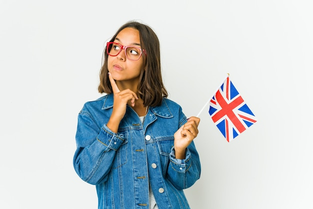 Thoughtful young latin woman holding the english flag