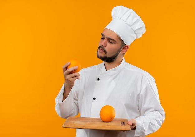 Giovane cuoco maschio premuroso in tagliere della tenuta dell'uniforme del cuoco unico e arancio che esaminano arancio isolato sullo spazio arancio