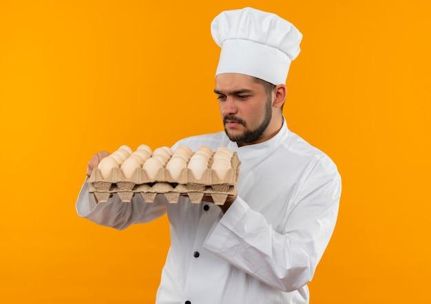 Giovane cuoco maschio premuroso in uniforme del cuoco unico che tiene e che esamina il cartone delle uova isolato sullo spazio arancione