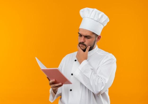 Giovane cuoco maschio premuroso in uniforme del cuoco unico che tiene e che esamina il rilievo di nota con la mano sul mento isolato sullo spazio arancione
