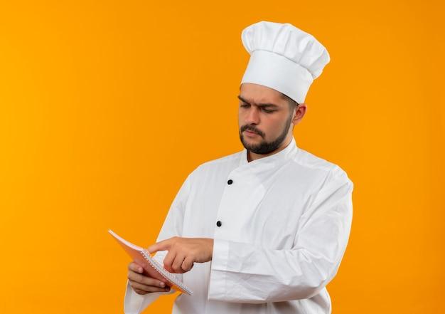 Giovane cuoco maschio premuroso in uniforme del cuoco unico che tiene che esamina e che mette il dito sul blocco note isolato sullo spazio arancione
